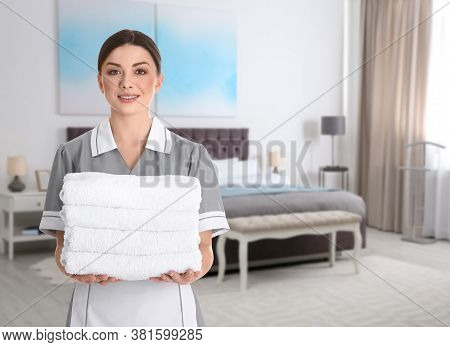 Beautiful Chambermaid With Clean Folded Towels Near Bed In Hotel Room
