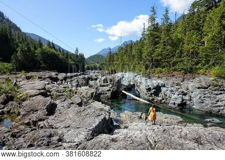 A Woman Exploring Wally Creek, On The Way To Tofino.  The Water Is Magical For Swimming, The Flowing