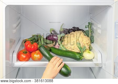 Hand Picks Up Zucchini From The Refrigerator Shelf. Hand Takes A Zucchini From The Refrigerator. The