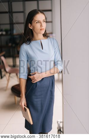 Beautiful Young Businesswoman Holding Paper Documents Folder While Standing Near Window In Modern Of