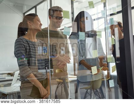 Brainstorming Concept. Group Of Happy Creative Business People Looking At Sticky Notes On Glass Boar