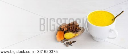Golden Milk In White Cup On Light Wooden Background. Copy Space. Ayurvedic Warm Beverage For Health