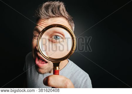 man see through magnifying glass on the black backgrounds. Big man eye