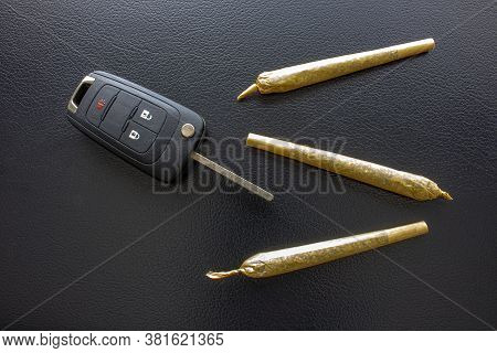 Cannabis Joints Cigarettes With Car Key On The Side On A Leather Black Texture. Concept Driving High