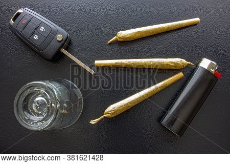 Cannabis Joints Cigarettes With Car Key, A Shoot Glass And A Lighter On A Leather Black Texture. Con