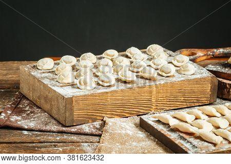 Semi-finished Russian Dumplings Pelmeni On The Wooden Board With Flour