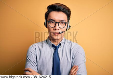 Young handsome chinese call center agent man wering glasses using headset skeptic and nervous, disapproving expression on face with crossed arms. Negative person.