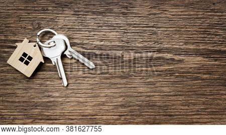 House Key Pair With House Shaped Keyring On Old Wooden Textured Background. Top View. Copy Space
