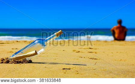 message in bottle in the sand and alone man looking at the sea view