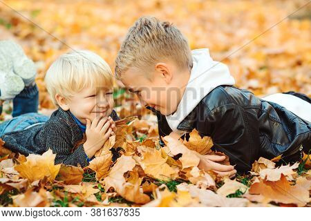 Smiling Happy Kids Lying On Autumn Leaves. Cute Brothers Resting In Autumn Park. Autumn Vacation. Ch
