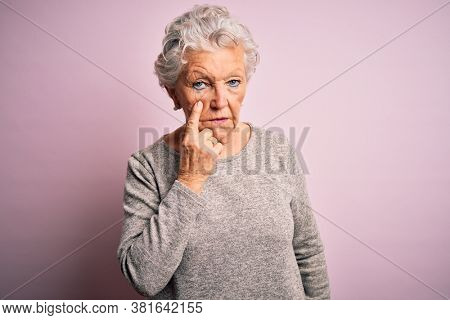 Senior beautiful woman wearing casual t-shirt standing over isolated pink background Pointing to the eye watching you gesture, suspicious expression