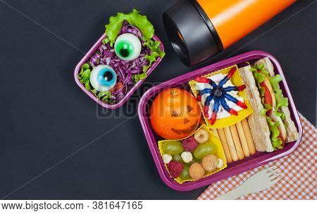 Open Halloween Lunch Box With School Lunch Near Thermo Mug On Black Background