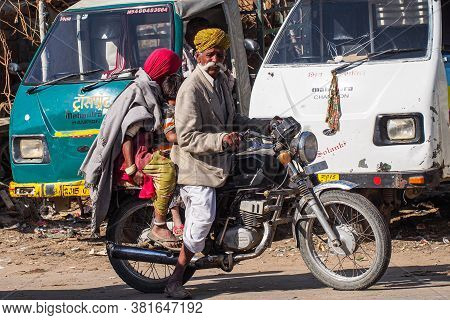 Jaisalmer, India - Dec 31, 2019: Indian Rajasthani People On Their Motorcycle In The Streets Of Jais