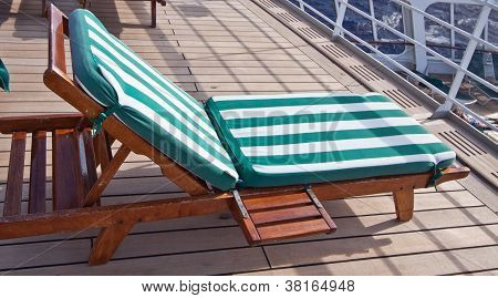 Comfortable wooden reclining cruise ship deck chairs with striped cushions to enjoy oneself and relax during a summer voyage