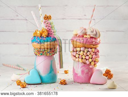 Two Freak Shakes Topping With Donut, Marshmallow, Popcorn And Marmalade Over Grey Background