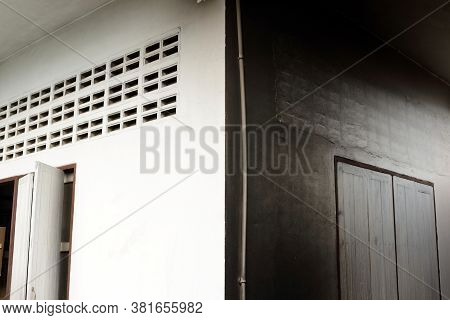The Wall Color Of The House Has One Side White And The Other Side Is Black Due To Soot.