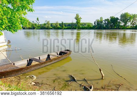 Old Wooden Fishing Boat Anchored On Improvised Dock On The River.