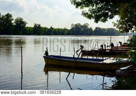 Silhouetted View On Fishing Boats Are Anchored On Improvised Dock On The River.