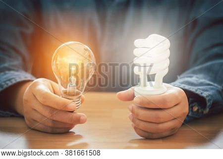 Hands Holding Light Buld And Spiral Bulb, Saving Energy Efficiency And And Accounting Finance Concep
