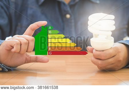 Hands Holding Spiral Bulb And Symbol Energy Efficiency, Saving Energy Efficiency And And And Green E