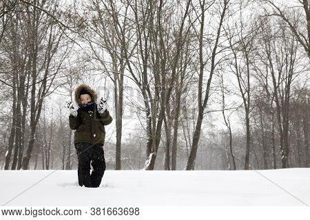 A Boy In Warm Clothes Walks In The Winter Park And Plays With The Snow, A Small Boy 5-6 Years Old