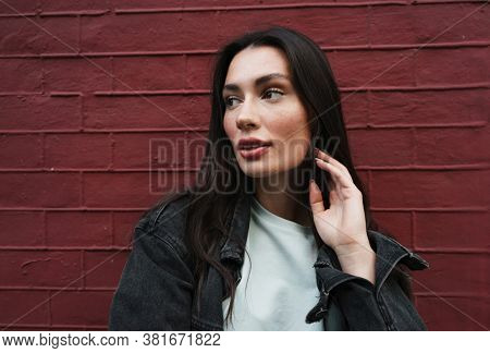 Image of beautiful young woman walking outdoors and looking away
