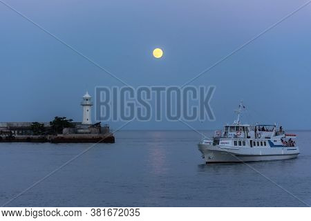 Full Moon Yalta With A View Of The Ship And The Lighthouse On July 04, 2020. Tourist Ship On The Bac