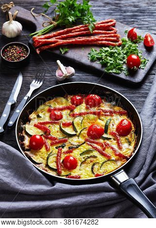 Frittata, Omelet With Zucchini, Thin Smoked Sausages And Tomatoes Filling In A Skillet On A Dark Woo