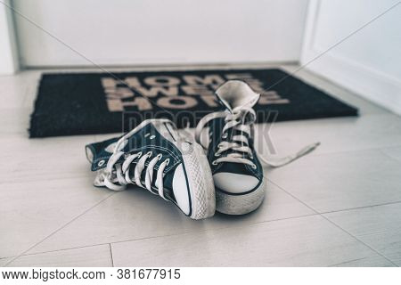 Leaving shoes on floor, at front door entrance outside home. Men removing their sneakers without placing them away. Tidy house cleaning concept.