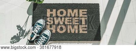 Home sweet home door mat at house entrance with women's sneakers of woman that has just arrived. New condo homeowner moving in with plant. Panoramic crop.