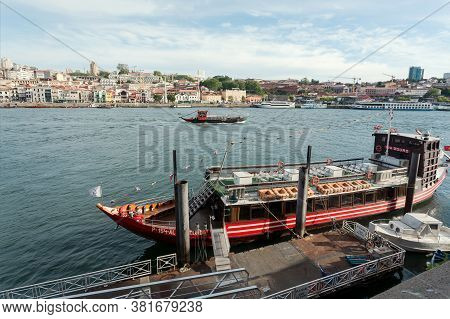 Porto, Portugal: Douro River And Riverboats Floating Past Old City On 19 May, 2019. Portuguese Langu