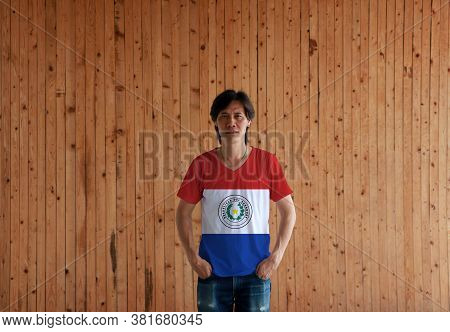 Man Wearing Paraguay Flag Color Shirt And Standing With Two Hands In Pant Pockets On The Wooden Wall