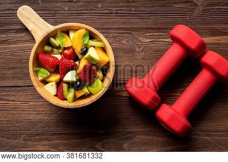 Healthy Fruits.  Fresh Fruits Salad Diet Slim Fit With Dumbbells Sport Equipment For Healthy Lifesty