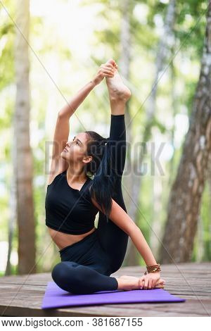 Beautiful Young Brunette Woman In Black Sportswear Practices Yoga, Doing Surya Yantrasana Exercise,