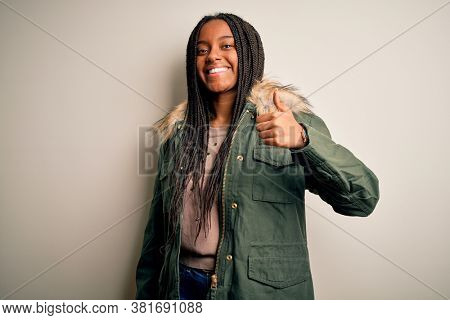 Young african american woman wearing winter parka coat over isolated background doing happy thumbs up gesture with hand. Approving expression looking at the camera showing success.