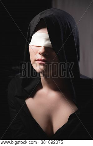 Portrait Of An Attractive Young Woman In A Hood And Black Cape With A Blindfold. Low Key Sexy Caucas