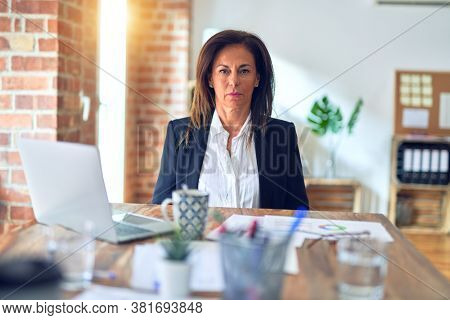 Middle age beautiful businesswoman working using laptop at the office with serious expression on face. Simple and natural looking at the camera.