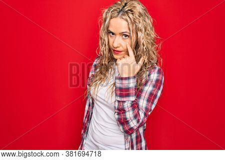 Young beautiful blonde woman wearing casual shirt standing over isolated red background Pointing to the eye watching you gesture, suspicious expression