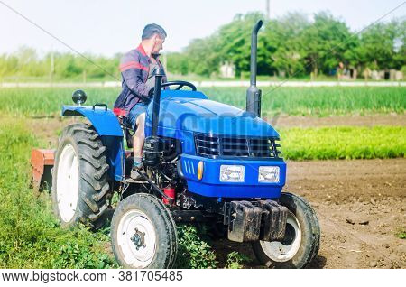 A Farmer Drives A Tractor While Working On A Farm Field. Loosening Surface, Cultivating The Land. Fa