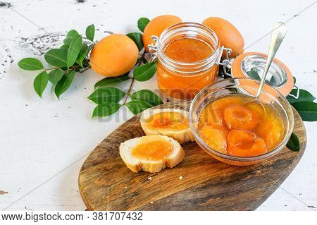 Sweet Homemade Apricot Jam In The Glass Jar And Bowl On The Wooden Kitchen Table. Sandwiches With Ap