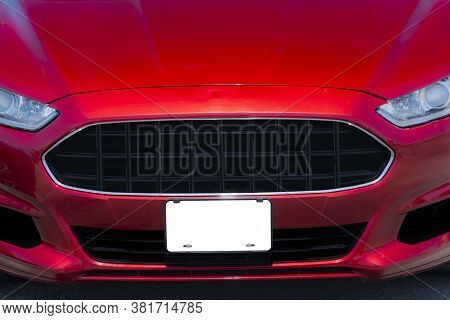 Horizontal Shot Of A Red Automobile With A Blank White Front License Plate With Copy Space.