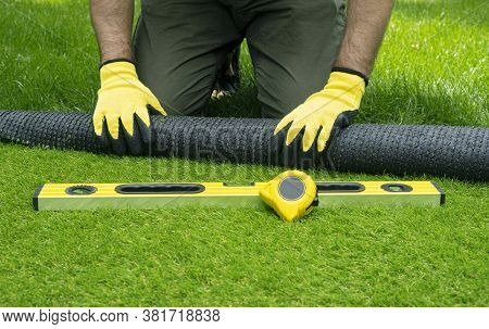 Landscaping Of The Yard With Artificial Turf. Male Hands Hold A Roll Of Artificial Grass.