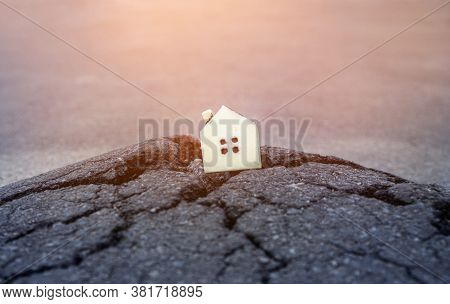 Miniature Toy House Standing On The Damaged Asphalt Road. Earthquake Destruction And Other Natural D