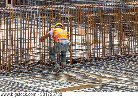 Steel Fixer Tying Steel Reinforcement Cage Together. Construction Worker Surrounded By Rebar.