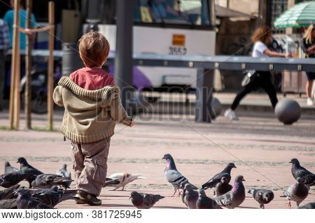 Timisoara, Romania - April 13, 2016: Kid Playing With Pigeons On The Street. Real People.