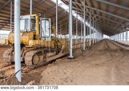 Bulldozer Is Pushing Soil In A Worksite. A Bulldozer Is Leveling The Ground In A Barn Under Construc