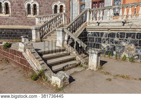 An Old Open Outer Stone Staircase. Stone, Cement Steps Of The Old Staircase With Traces Of Weatherin