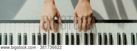 Woman learning to play piano at home on digital keyboard. Panoramic banner crop of hands playing beginner chords to learn playing by herself.