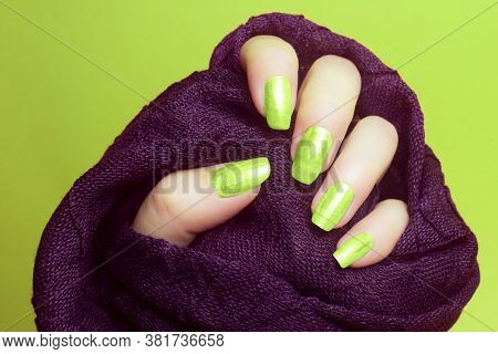 The Female Hand With Neon Green Nails Is Wearing A Purple Fabric On Green Background, Manicure And N