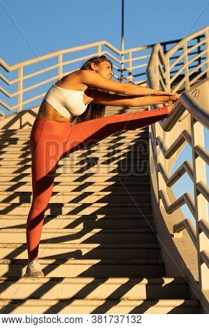 Athletic Woman In Pink Leggings Standing On Stairs, Stretching Muscles Making Functional Training, D